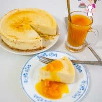 A slice of classic mango cheesecake on a plate with mango filing