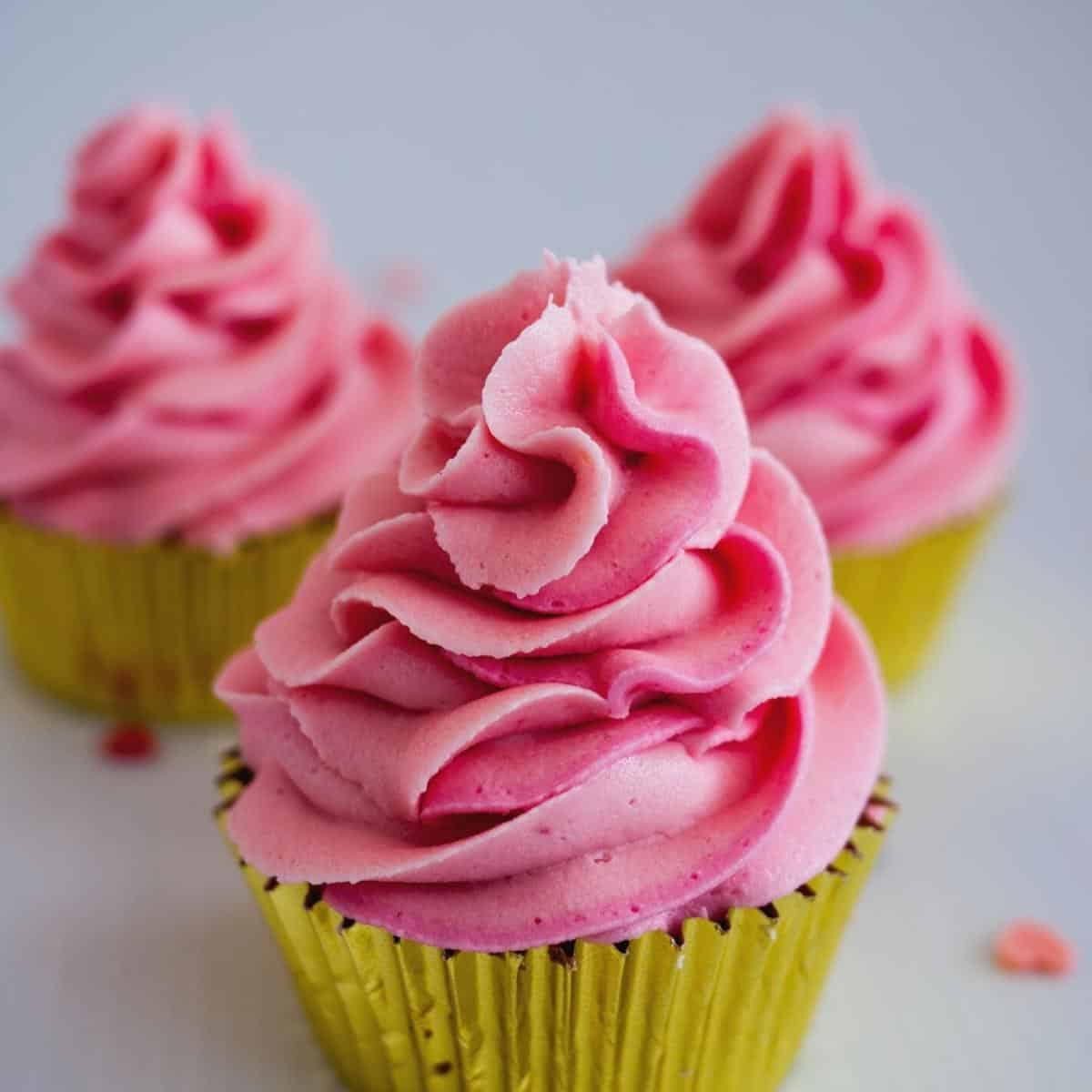Three frosted cupcakes in pink champagne