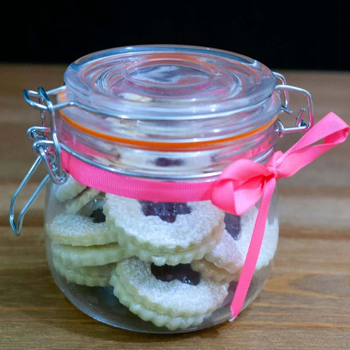 Linzer jam cookies in a holiday gift jar
