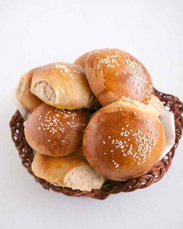 Whole wheat hamburger buns in a bread basket.