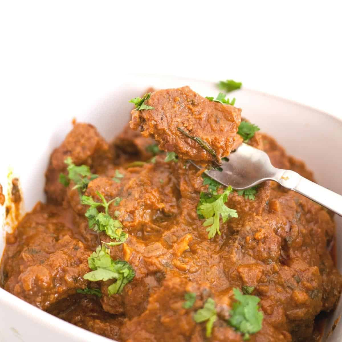 Beef curry in a white serving dish.