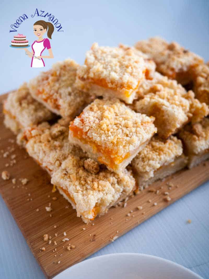 A stack of apricot crumble bars on a wooden board.