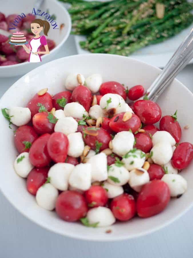 This salad with tomato and Mozzarella  is a great twist on the Italian Classic Caprese Salad with toasted pine nuts. Simple, Easy and always refreshing this salad takes  less than five minutes to put together.