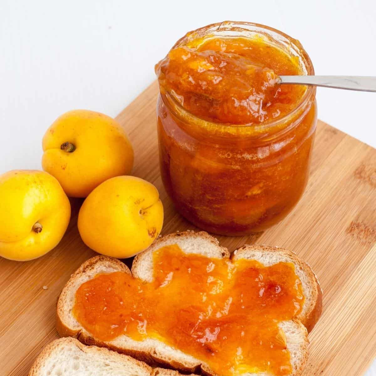 jar with apricot jam and slice with jam.