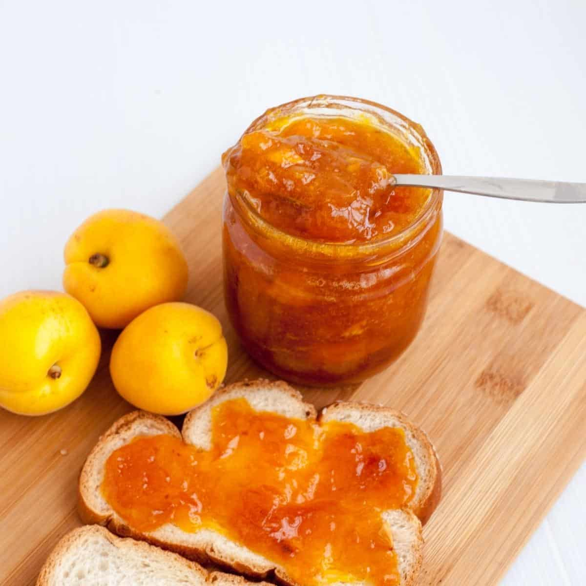 Fresh apricots, jam and slice of bread with jam.