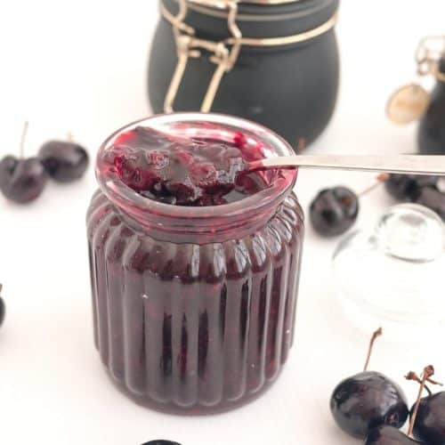 A mason jar with cherry fruit filling.