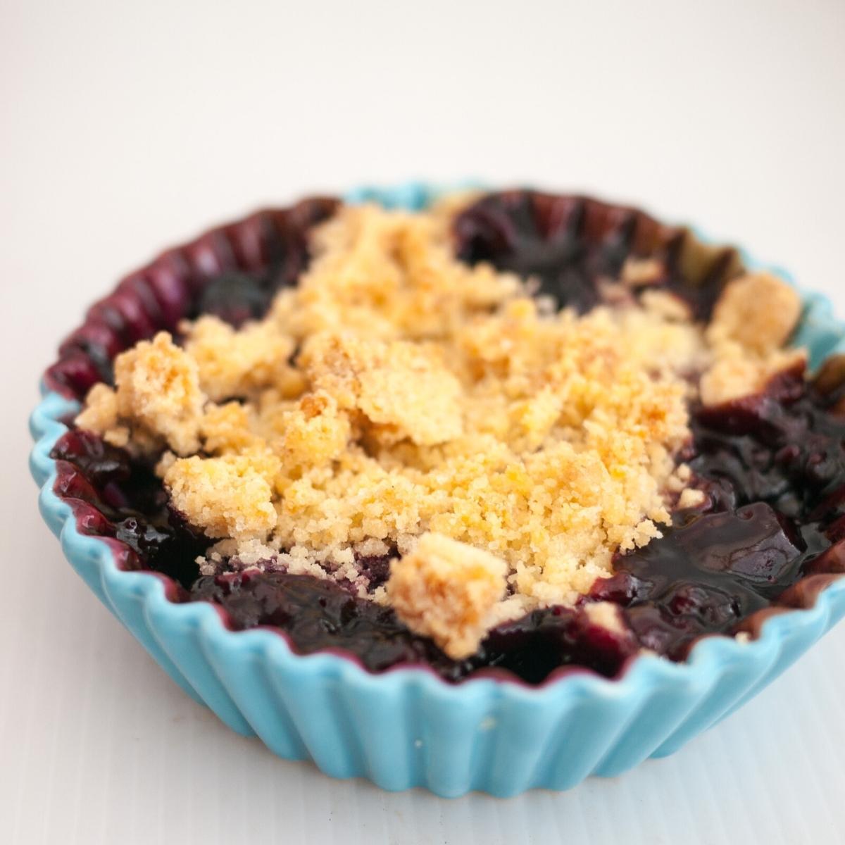 A ramekin with blueberry fruit crumble.