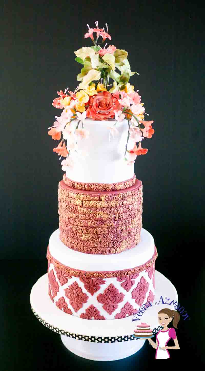 A decorated wedding cake with sugar flowers on top.