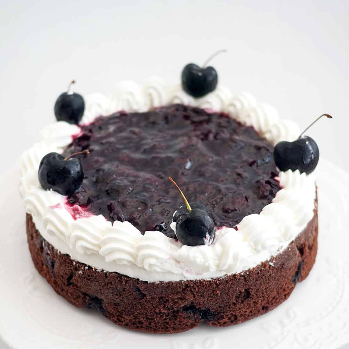 A chocolate cake with cherry filling and whipped cream.