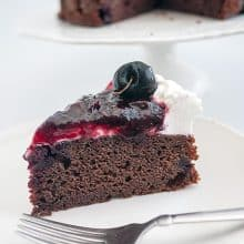 A slice of cherry cake with chocolate and cherry filling.