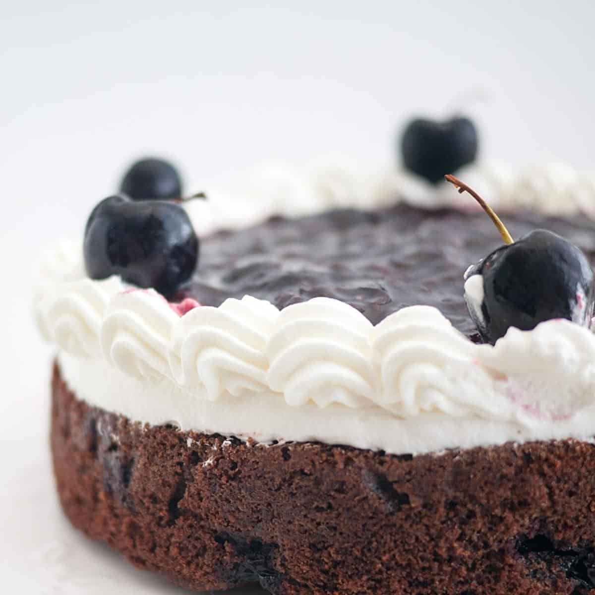 A layer of chocolate cake with fresh cherries.