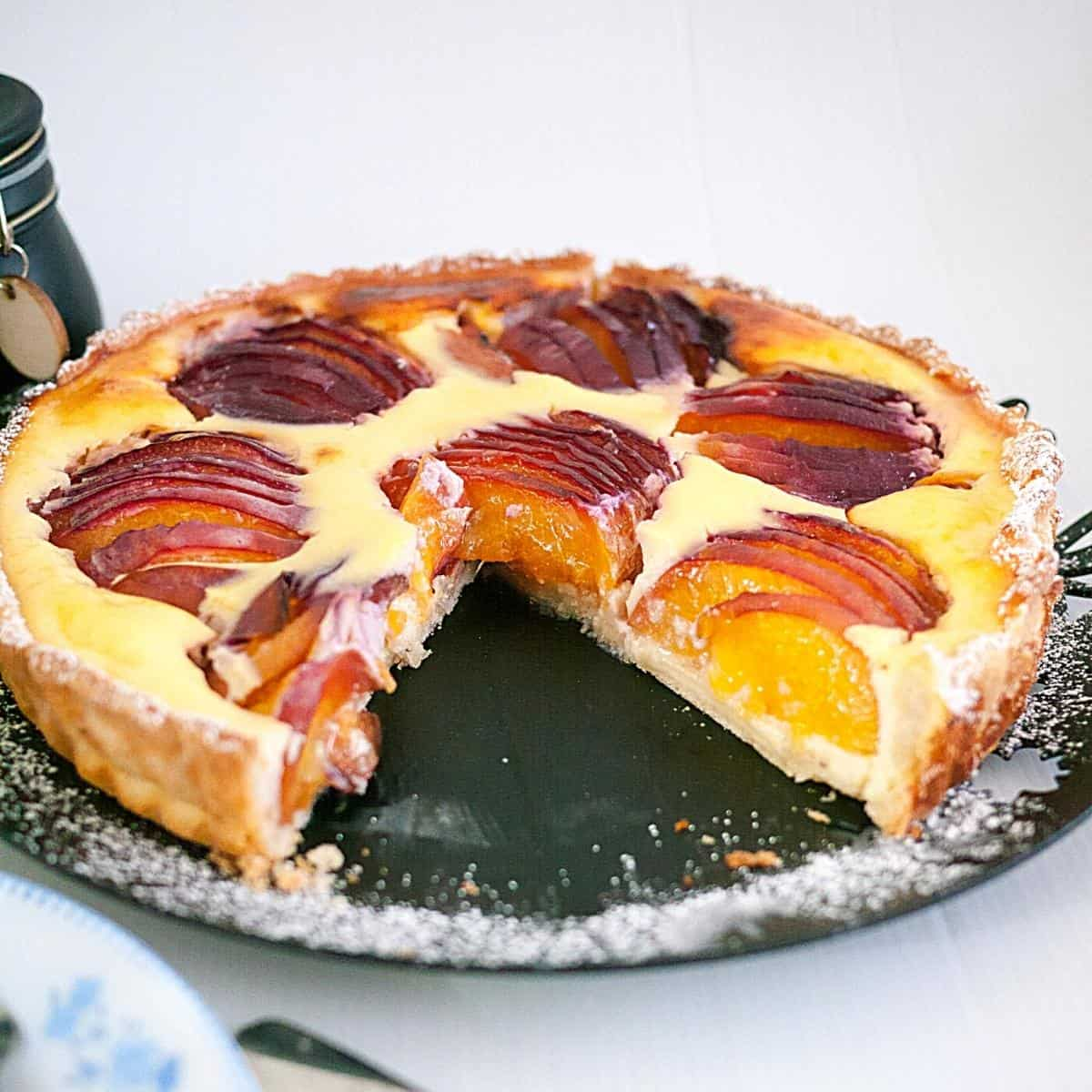 A sliced nectarine tart on a plate.