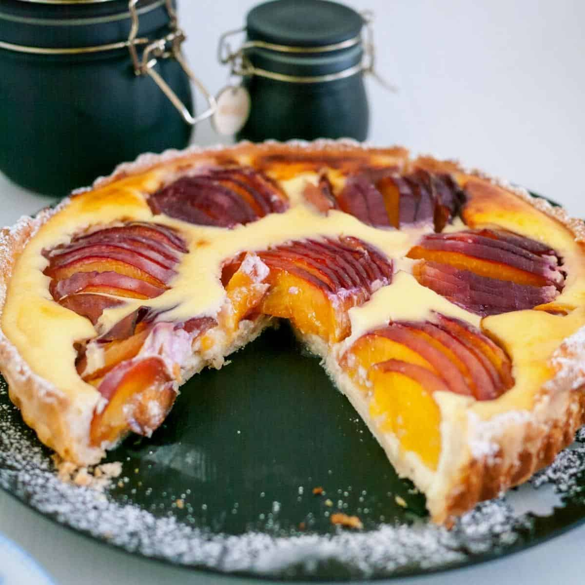 A tart with nectarines on a table.