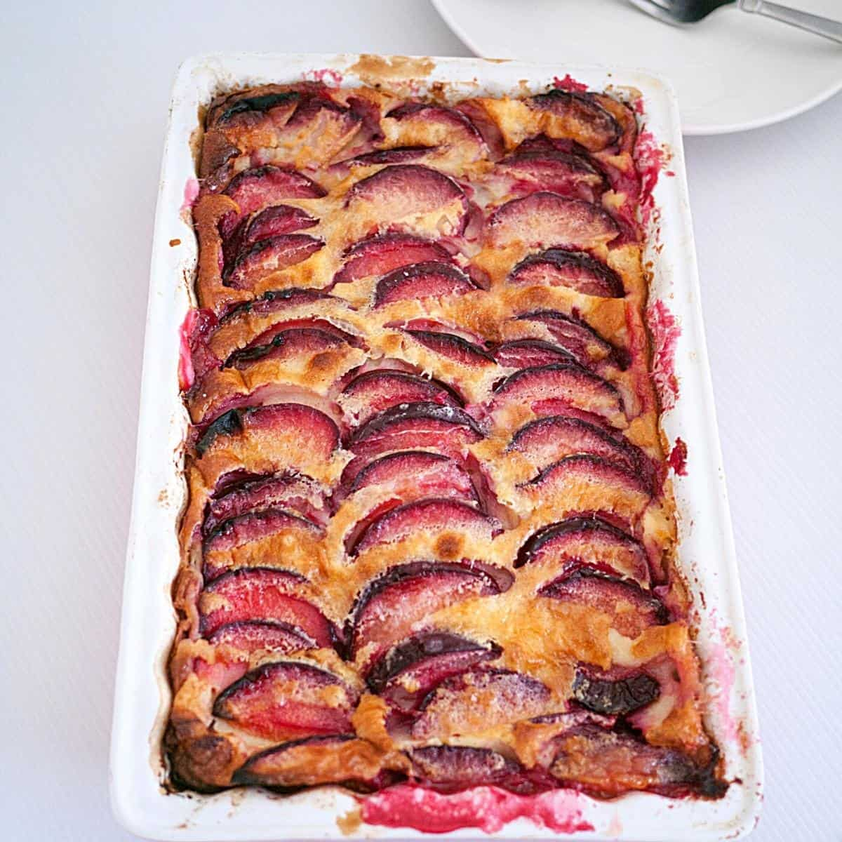 A baking dish with baked clafoutis with plums.
