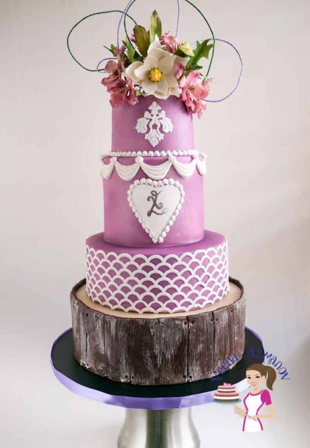 A violet wedding cake with sugar flowers on top.