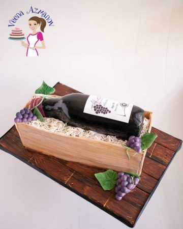A decorated cake shaped like a wine bottle in a wooden box.