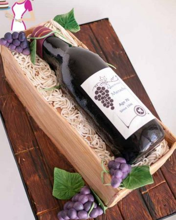 Novelty cake wine bottle and crate on a cake board.