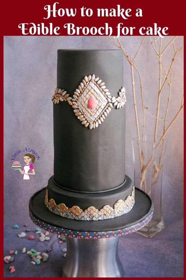A brooch decorated black fondant cake.
