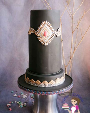 A brooch decorated black fondant cake.