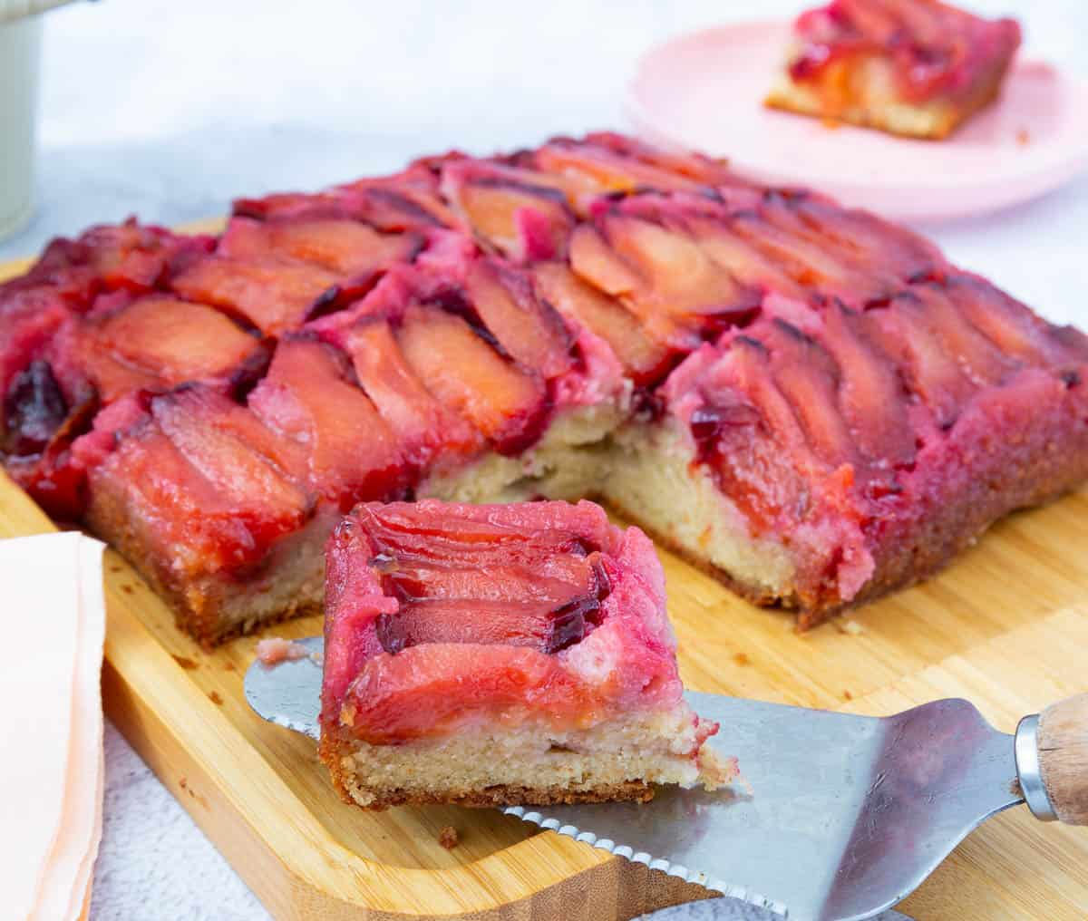 Slice of plum cake on a cake board.