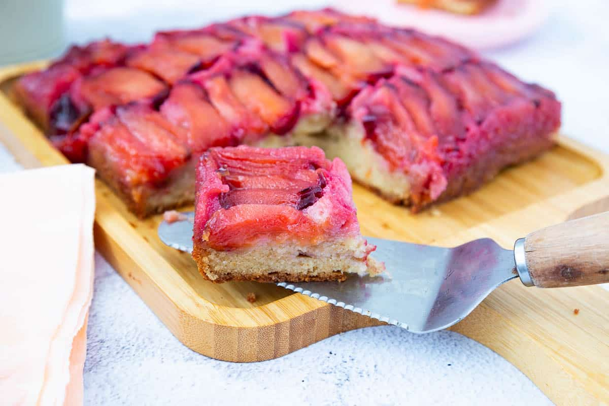 A slice of plum cake on a wooden boards.