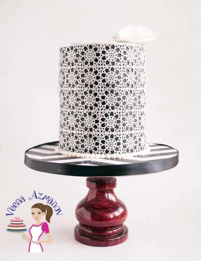 A black and white lace decorated cake on a stand.