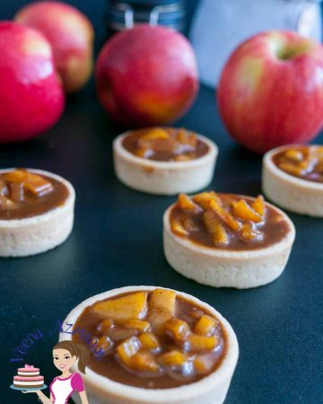 Top angle of the tarts - Rich, creamy, fruity and caramelized these exotic cinnamon caramel apple tarts are an absolute treat. Filled in crisp short crust pastry baked to perfection. These are perfect fir fall or any time of the year mini desserts and make entertaining a breeze.