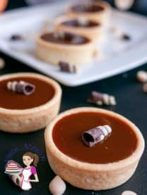 Another view of my These white chocolate pumpkin caramel tarts made with sweet caramel enriched with the seasons pumpkin puree and pumpkin spice. They are simple easy and effortless. Weather you want to go semi homemade or baked from scratch these are an elegant way to entertain or dress a dessert table.