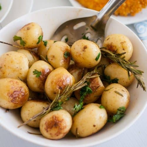 A white bowl with roast potatoes