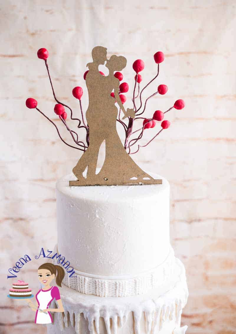 A Classic Winter Wedding Cake inspired by the knit wear. Nothing says winter better than winter clothing and this cake has it all in plenty.  All white cake with the effect of snow and a pop of red Christmas berries and leaves.