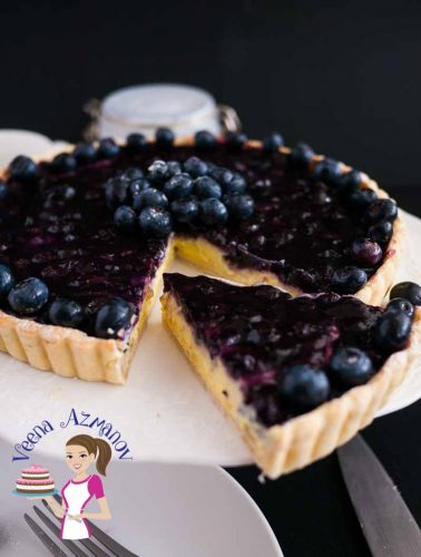 A blueberry tart on a cake stand.