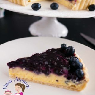 This blueberry tart is an absolute classic and luxurious dessert with rich, creamy vanilla pastry cream in a buttery short crust pastry, topped with a delicious blueberry compote and garnished with fresh blueberries. A simple, easy and effortless recipe that can be done a head of time.