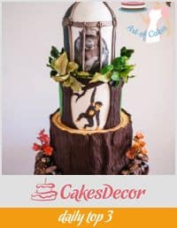 A cake decorated to look like a chimpanzee on a tree.