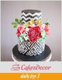 A cake decorated in a black damask design.