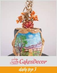 A cake decorated with a painting of a landscape scenery.