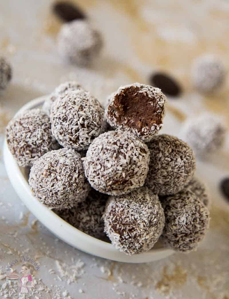A stack of coconut chocolate truffles in a small plate.