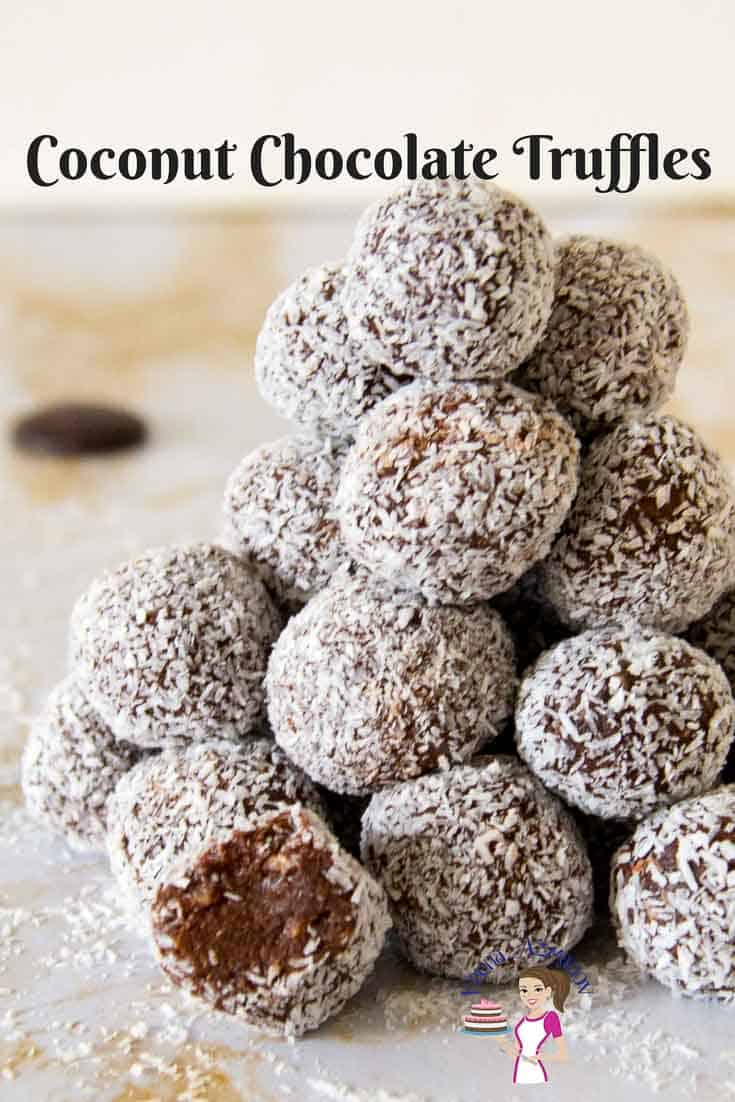 An Image showing a pile of coconut chocolate truffles with one showing the inside chocolate of the truffle