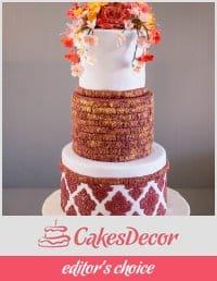 A cake decorated in a burgundy damask design.