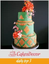 A cake decorated in a gold and green damask design.