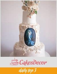 A wedding cake designed with a painting of a couple on the beach.