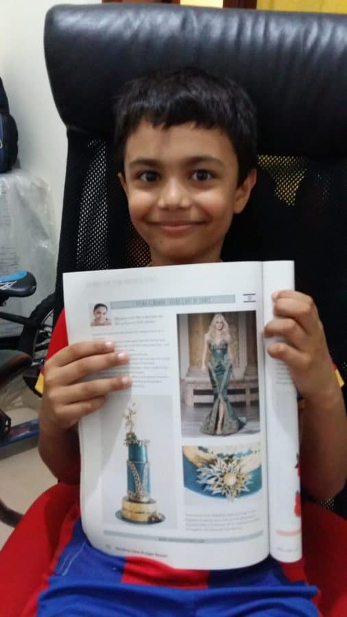 A boy showing a page from a cake decorating magazine.