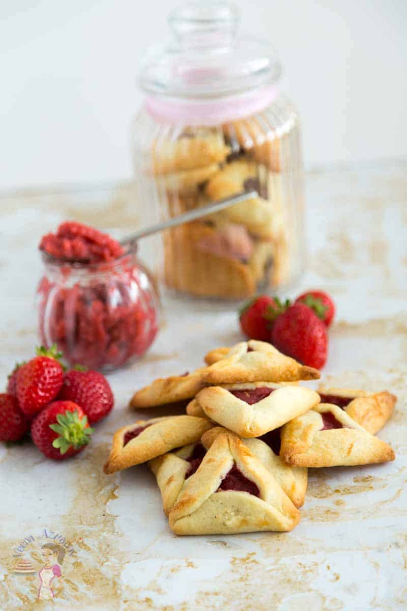 A collection of eggless hamentaschen cookies sharing the strawberry filling jar made with fresh strawberries.
