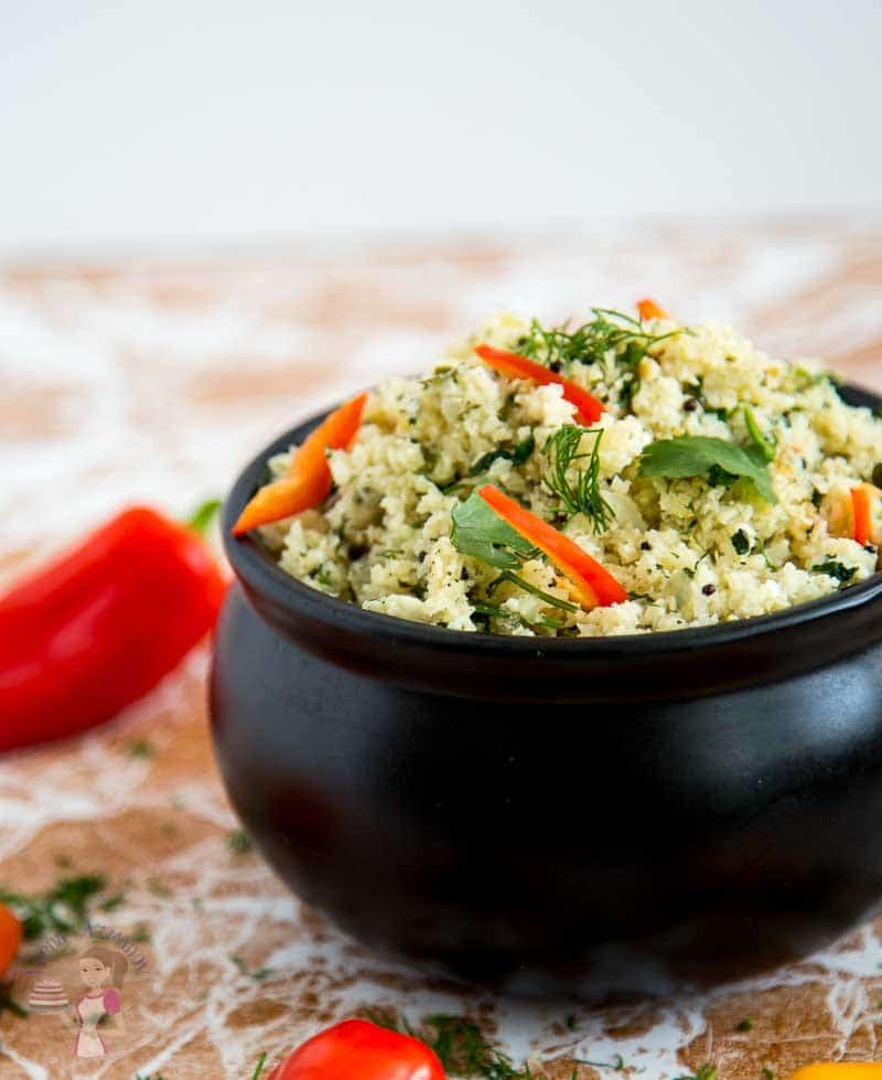 A half image of a pot of cauliflower rice - suateed with mustard seeds and dill garnished with jelepeno peppers