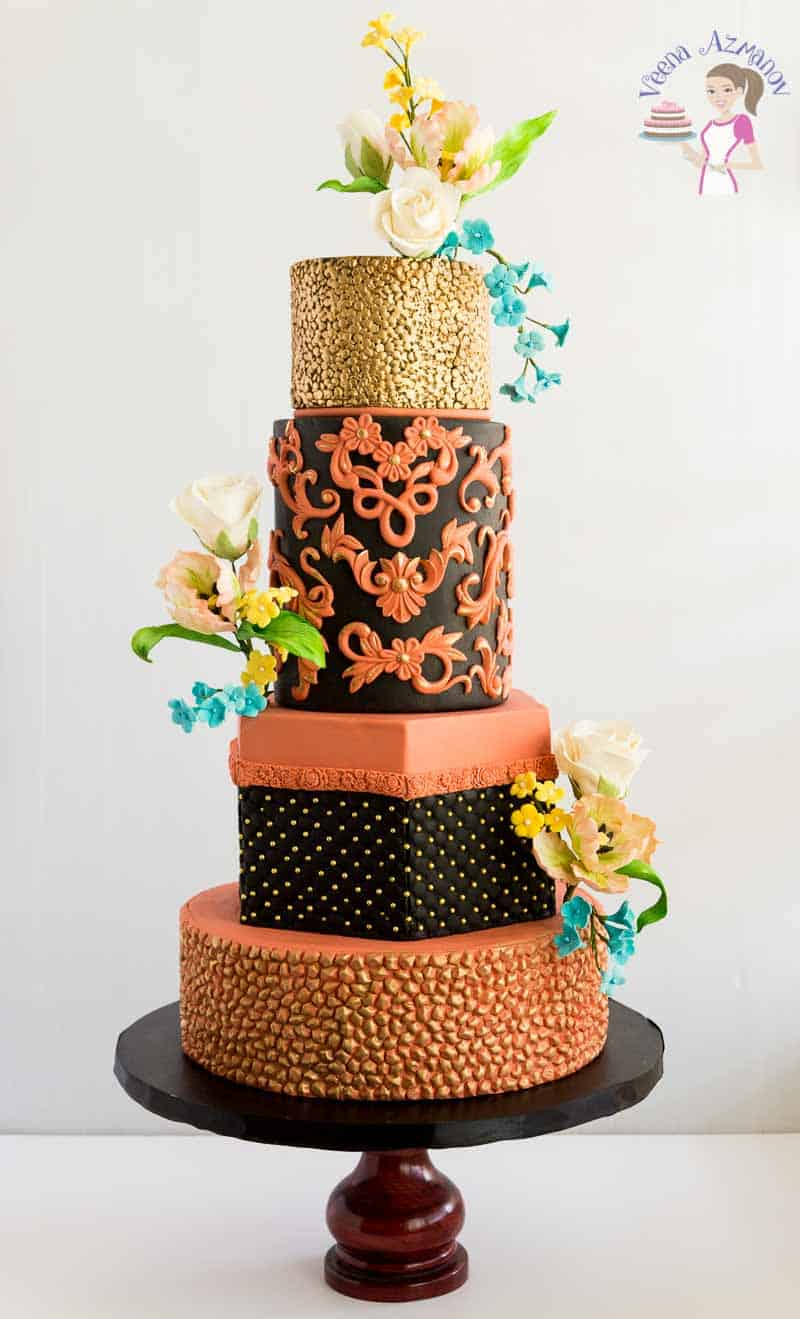 A Coppertone and black wedding cake made using Marvelous Molds new Simpress collections. This copper simpress wedding cake makes a bold display accompanied with black, accented with metallic gold dragees and adorned with sugar tulips, roses, and blossoms in blue, ivory and whites.