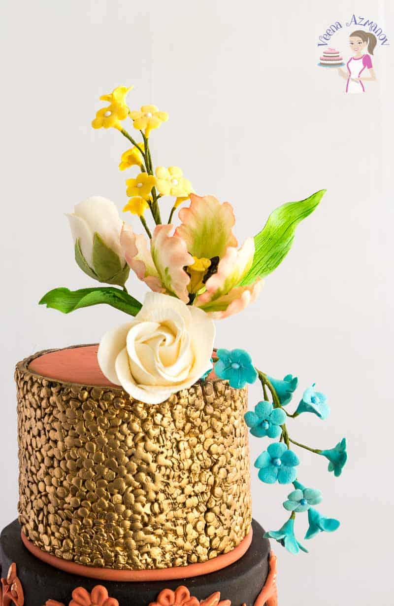 Top tier of the copper Simpress Wedding Cake with the simpress confetti collection adorned with sugar rose, sugar tulip and blossoms
