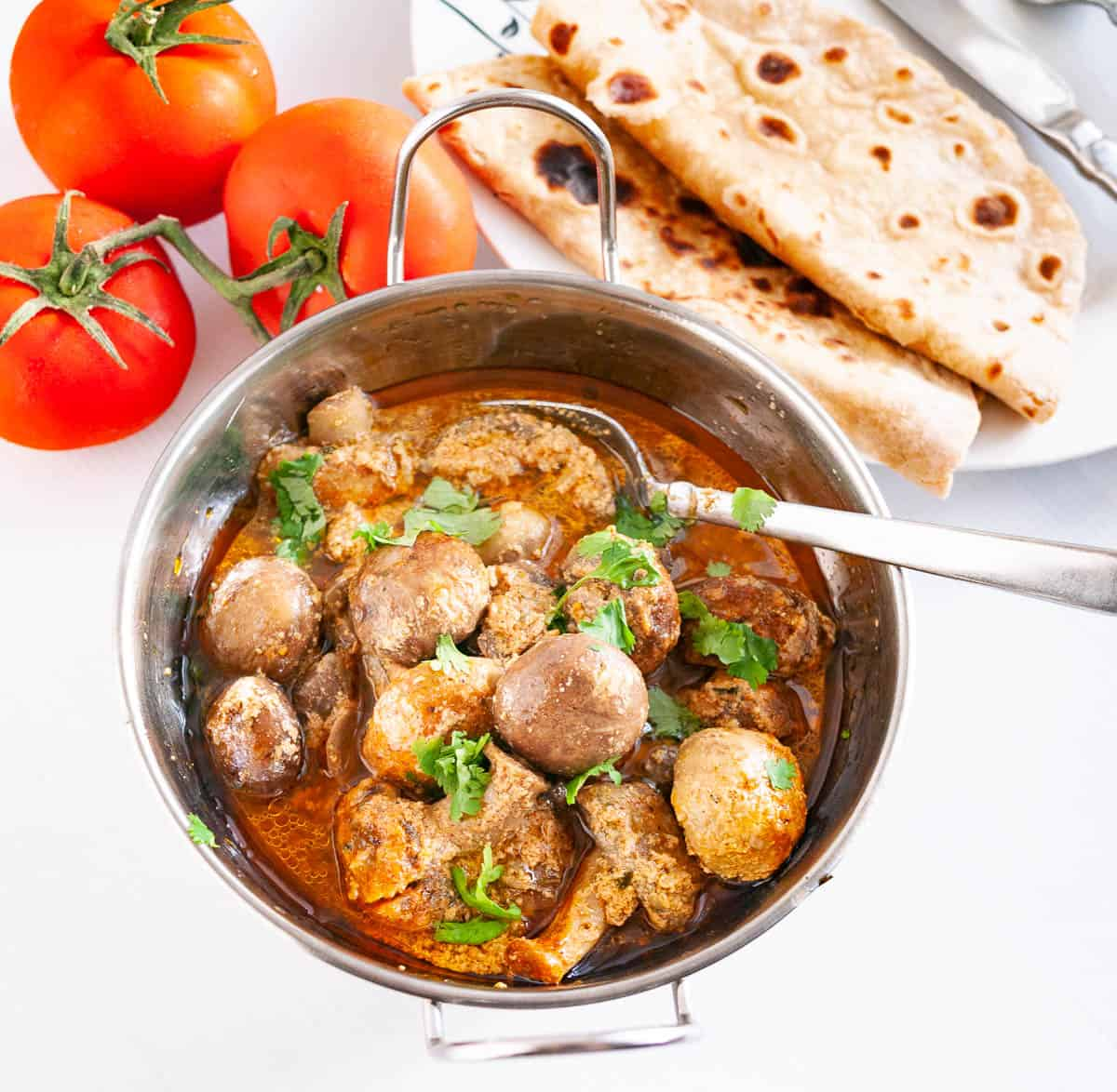 A pan with mushroom curry and chapati.