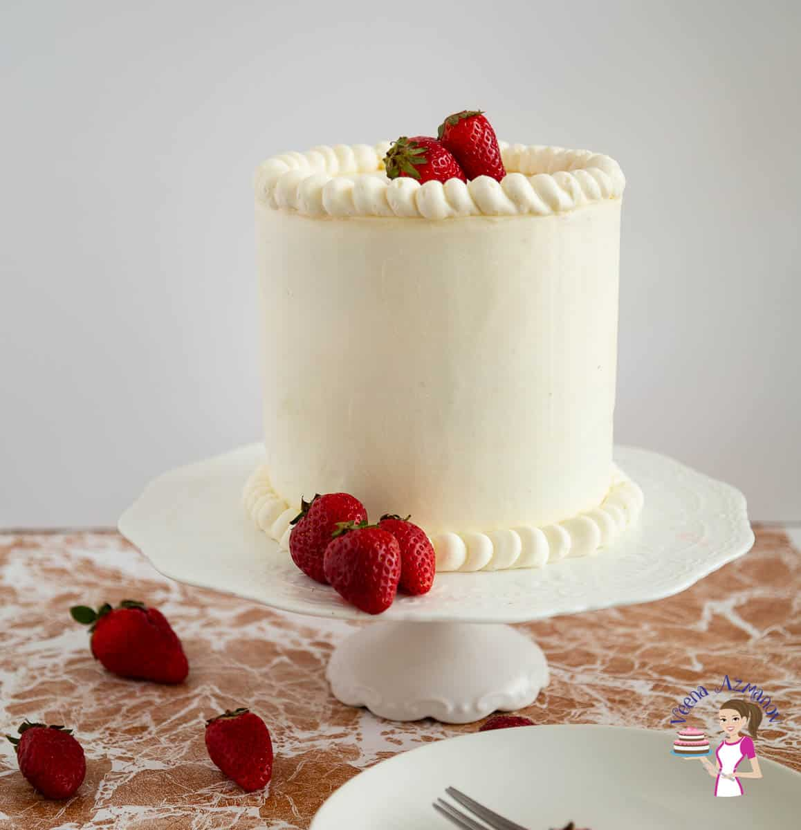A frosted cake on a cake stand with fresh strawberries