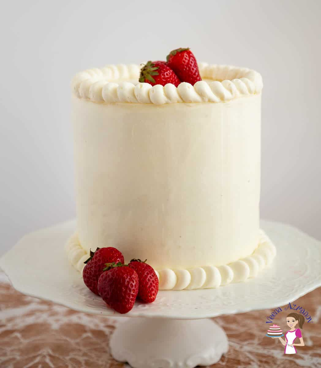 A frosted strawberry cake with fresh strawberries