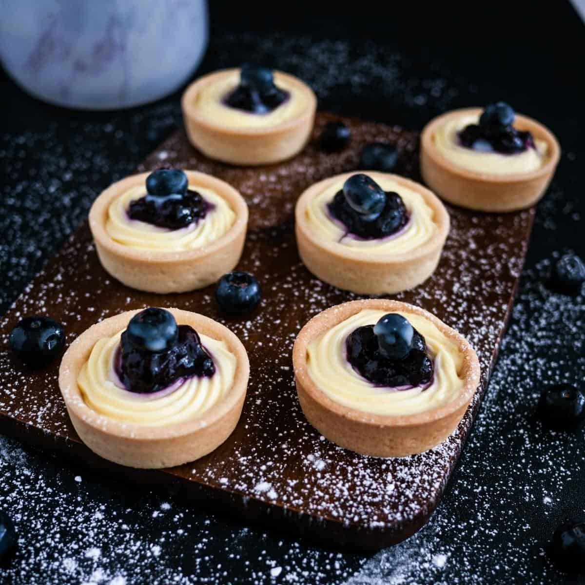 A wooden board with tartlets.