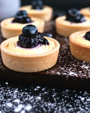 Mini tarts with cream cheese and blueberry filling a wooden board.